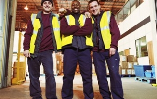 Three men in warehouse, smiling, portrait
