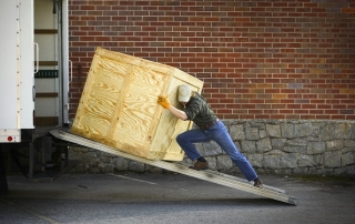 Young man pushing wooden crate up ramp to lorry