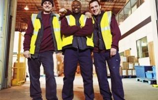 Three men in warehouse, smiling, portrait