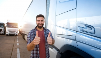 Middle aged professional trucker holding thumbs up and standing by his truck. Happy truck driver. Transportation services.