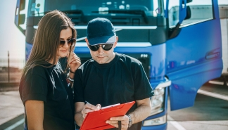 Two professional truck drivers stand in front of the big truck. They talk and perform a technical inspection of the vehicle before next drive. Professional transportation concept.
