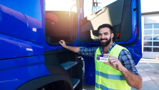 Truck driver candidate showing CDL driving license for transportation vehicles. Successfully passed training driving exam.